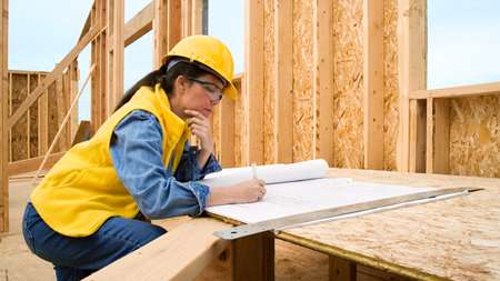 A photo of a construction worker looking over building plans.