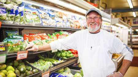 Photo of grocery shop owner in front of refrigeration equipment